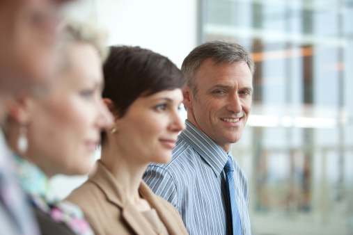 Smiling businessman in row of business people