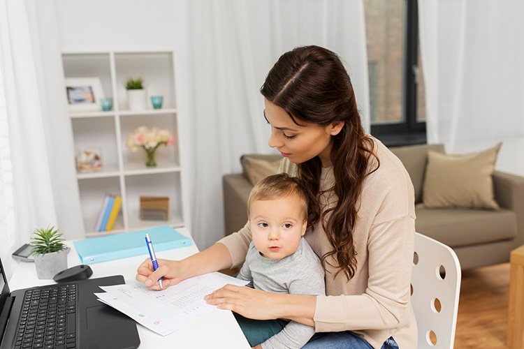 photo of an Alberta mother with her child, calculating her financials in preparation of her meeting with Agnes Leung, Chartered Business Valuator